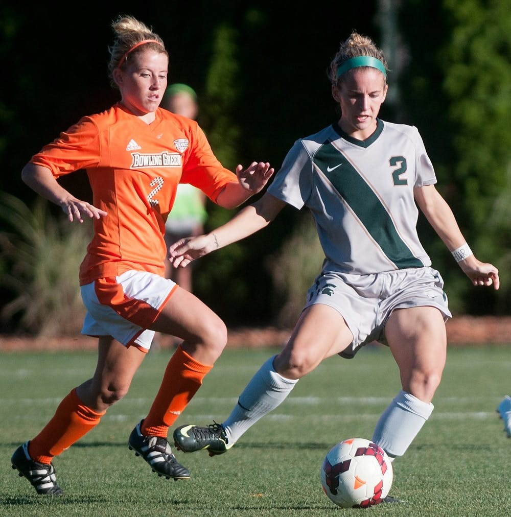 <p>Sophomore forward Allyson Krause prepares to pass the ball while Bowling Green midfielder Ashley Garr tries block the pass during the game on Sept. 13, 2013 at DeMartin Stadium at Old College Field. The Spartans defeated the Falcons, 3-1. Georgina De Moya/The State News</p>