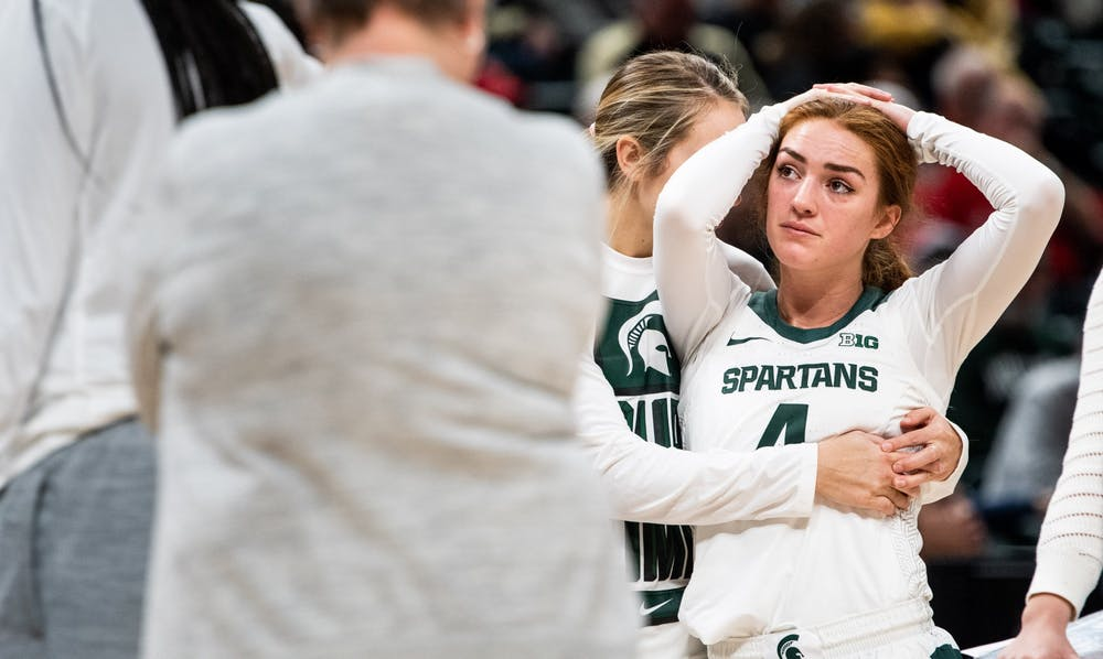 Redshirt junior Laurel Jacqmain puts her arms around a teary-eyed Taryn McCutcheon (4) during the game against Purdue at Bankers' Life Fieldhouse in Indianapolis March 5, 2020. The Spartans fell to the Boilermakers, 72-63.