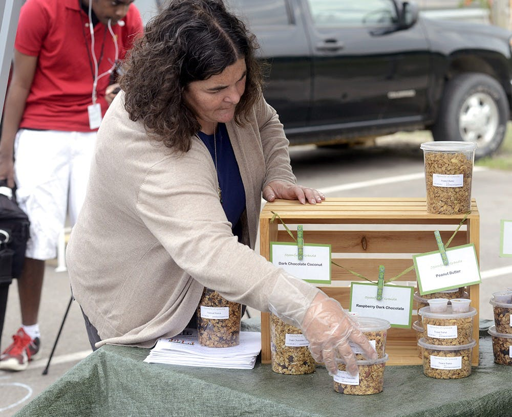 """<p>Sara Beer sets up her display for her stand """"Spoonful of Granola"""" for the customers of this year's East LansingFarmer's Market June 6th, 2015 in Valley Court Park. Wyatt Giangrande/State News</p>"""