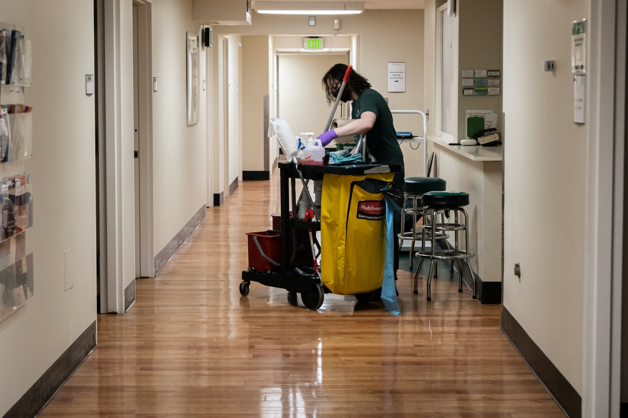 A person wearing a face mask and purple medical gloves looks into a cleaning supplies cart while standing in a medical building hallway.