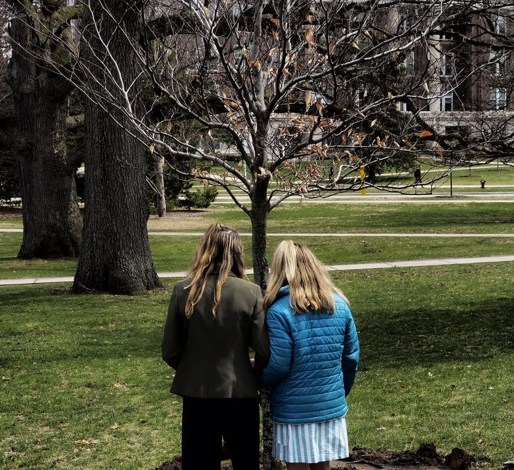 """Sister Survivors Amanda Cosman and Mimi Wegener stand in front of the newly planted """"Survivor Tree"""" during the Survivor Tree Dedication Ceremony east of the MSU Museum building on April 16, 2019. The tree planting ceremony is to honor survivors and family's members effected by sexual violence."""