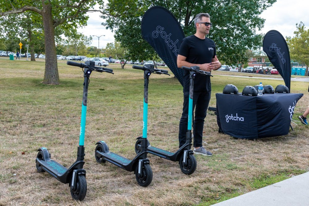 <p>Gotcha CEO and founder Sean Flood stands next to three Gotcha scooters on Aug. 28, 2019. </p>