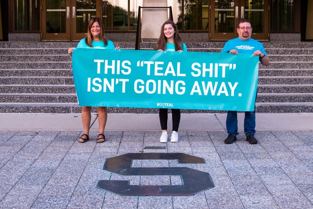 <p>Leslie Miller, Emma Ann Miller, and Bryan Tarrant (left to right) pose with a sign they brought outside of the Hannah Administration Building before &nbsp;the Board of Trustees meeting on Aug. 31, 2018. Emma Ann (daughter of Leslie) is a Nassar survivor herself, and Tarrant's daughter, Jessica Tarrant, is also a Nassar survivor.</p>