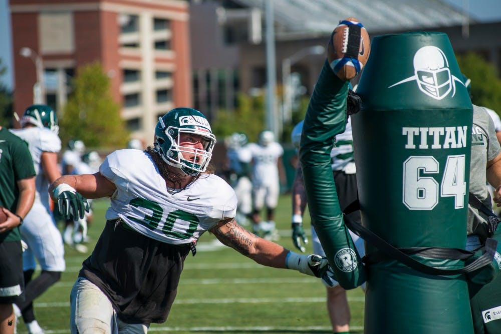 Senior linebacker Riley Bullough (30) goes after the ball in a drill during fall practice on Aug. 10, 2016 at the practice fields behind the Duffy Daugherty Football Building.