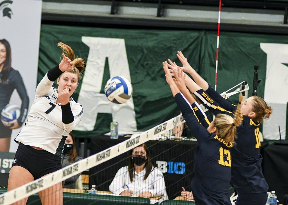 <p>Freshman outside hitter Sarah Franklin (7) attempts to hit the ball during the game against Michigan on Feb. 17, 2021 at the Jenison Fieldhouse. The Wolverines defeated the Spartans 3-1.</p>