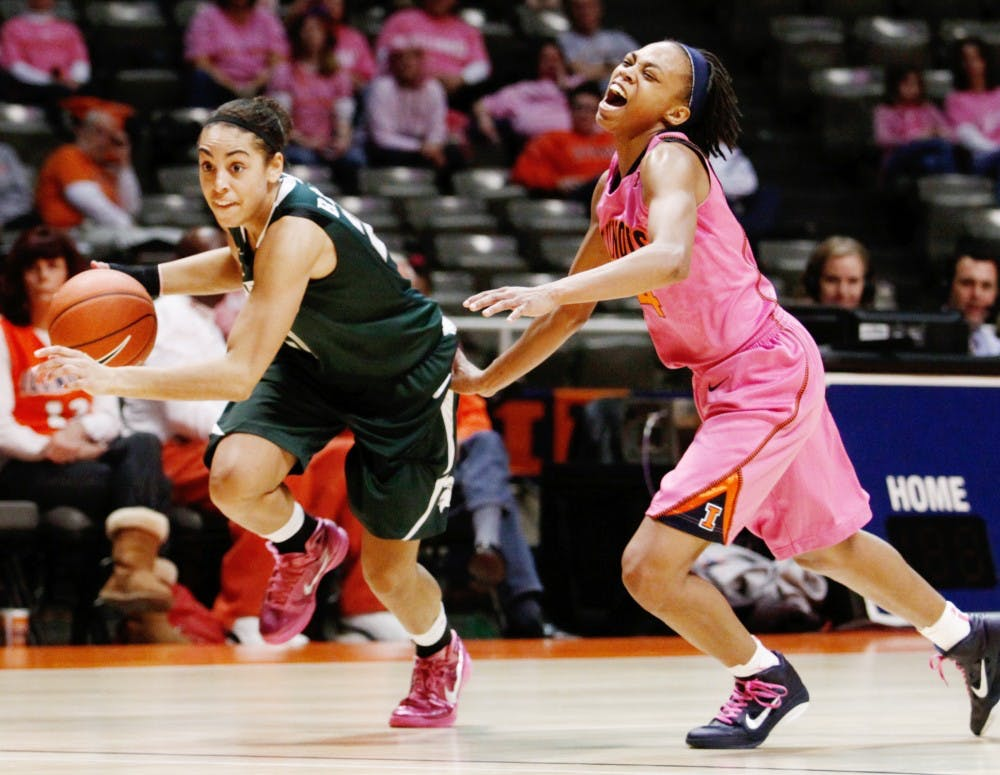 Senior guard Brittney Thomas drives the ball past Illinois guard Adrienne GodBold on Sunday afternoon at the Assembly Hall in Champaign, Ill. The Spartans defeated the Fighting Illini, 69-56, to clinch a share of the Big Ten Conference title. Daryl Quitalig/The Daily Illini