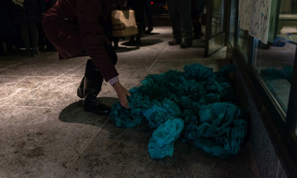 <p>Members of the audience ended the rally by laying teal paper flowers at the foot of a banner reading &quot;Courage&quot;  at the Hannah Administration Building on Jan. 24, 2019. The demonstration was held on the one-year anniversary of Larry Nassar being sentenced to 40 to 175 years in prison.</p>