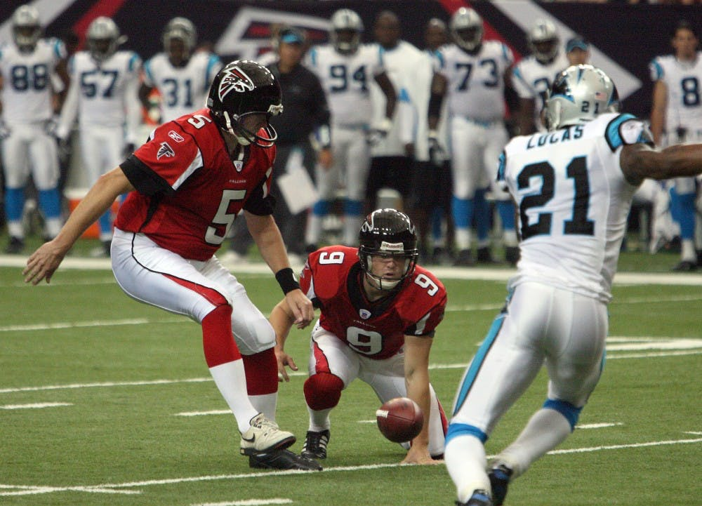 Atlanta Falcons punter Michael Koenen (9) fumbles the snap as Falcons kicker Morten Andersen (5) lines up for the attempted field goal, as Carolina Panthers cornerback Ken Lucas (21) charges in on the play in the first quarter. The Panthers defeated the Falcons, 27-20, at the Georgia Dome in Atlanta, Georgia, Sunday, September 23, 2007. (Curtis Compton/Atlanta Journal-Constitution/MCT)