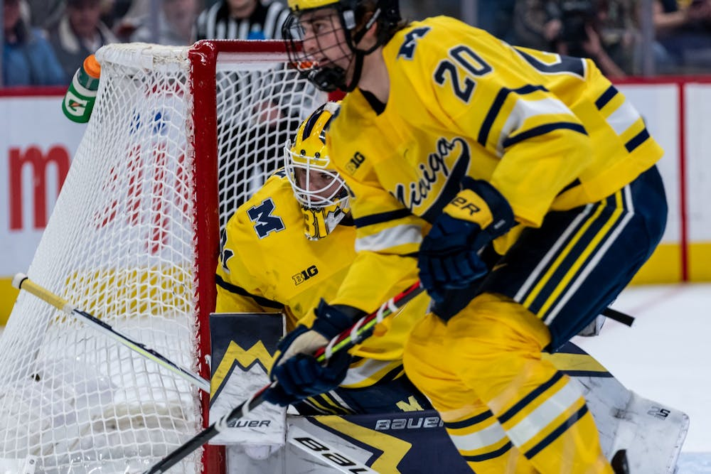 Michigan goaltender Strauss Mann (left) watches the puck in the corner. The Spartans fell to the Wolverines, 1-4, at Little Caesars Arena on February 17, 2020.