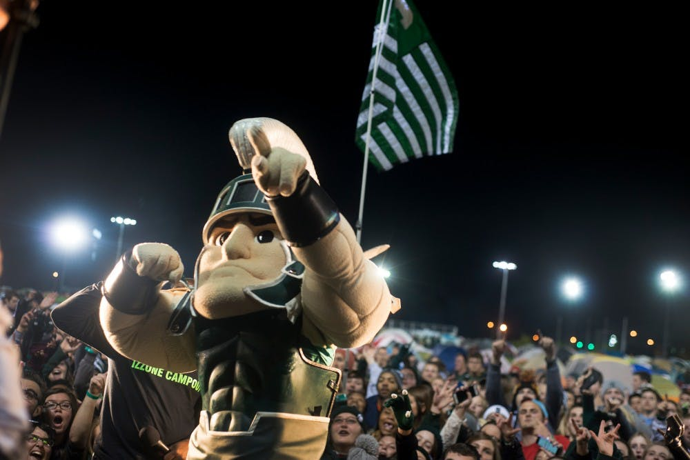 <p>Sparty poses for a picture with students behind him on Oct. 9, 2015, during the Izzone Campout at Munn Field. This annual event consists of students staying throughout the night in hopes of getting lower bowl seating. </p>