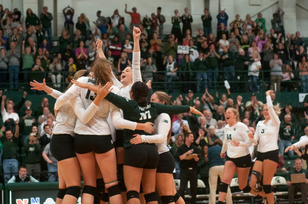 <p>Senior setter Halle Peterson celebrates the victory with her team at the volleyball game against the Michigan on Sept. 30, 2015 at Jenison Field House. The Spartans defeated the Wolverines, 3-0. </p>