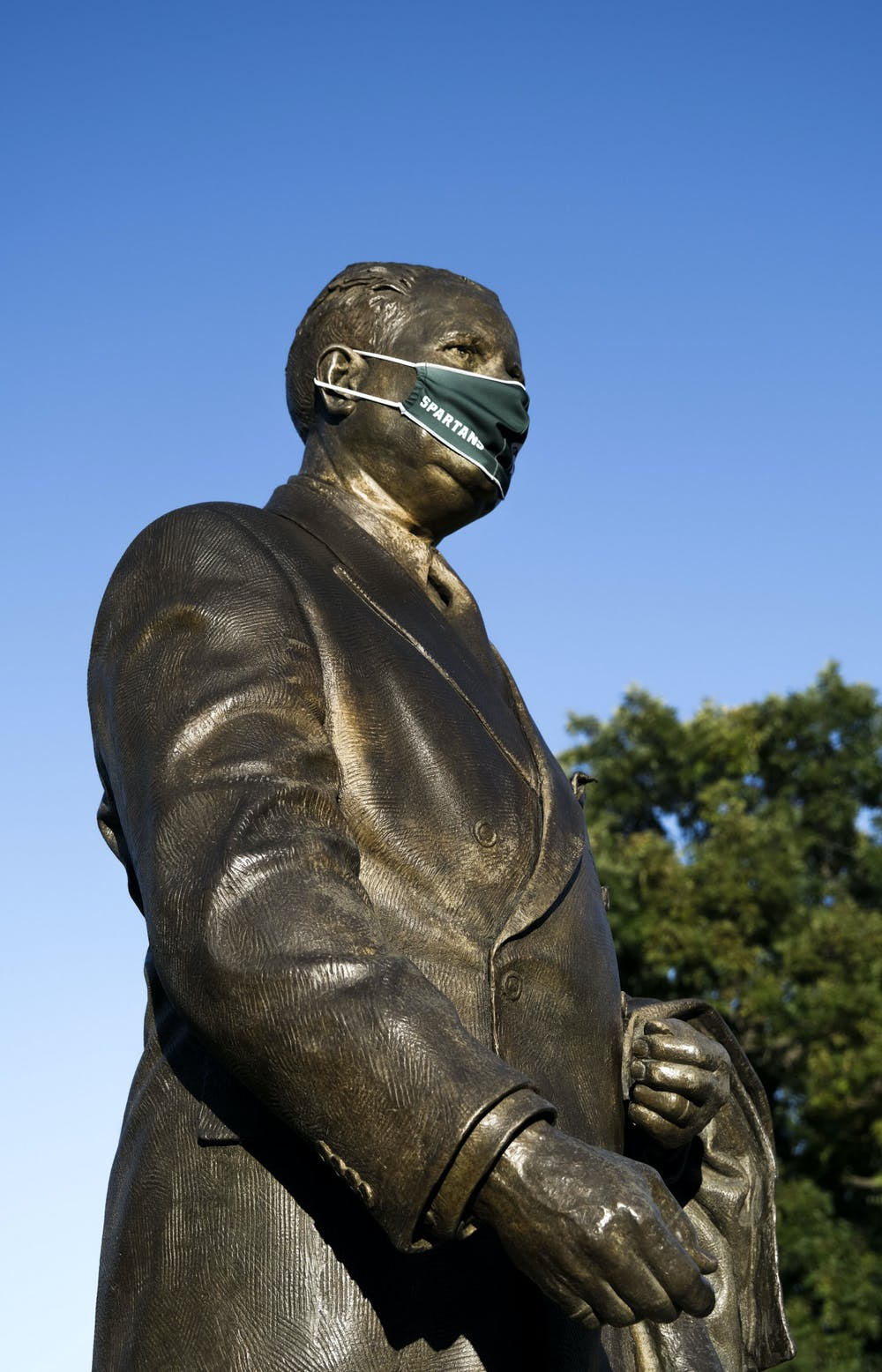 <p>Statue of President John A. Hannah with a mask on in front of the Hannah Administration Building on Sept. 20, 2020.</p>