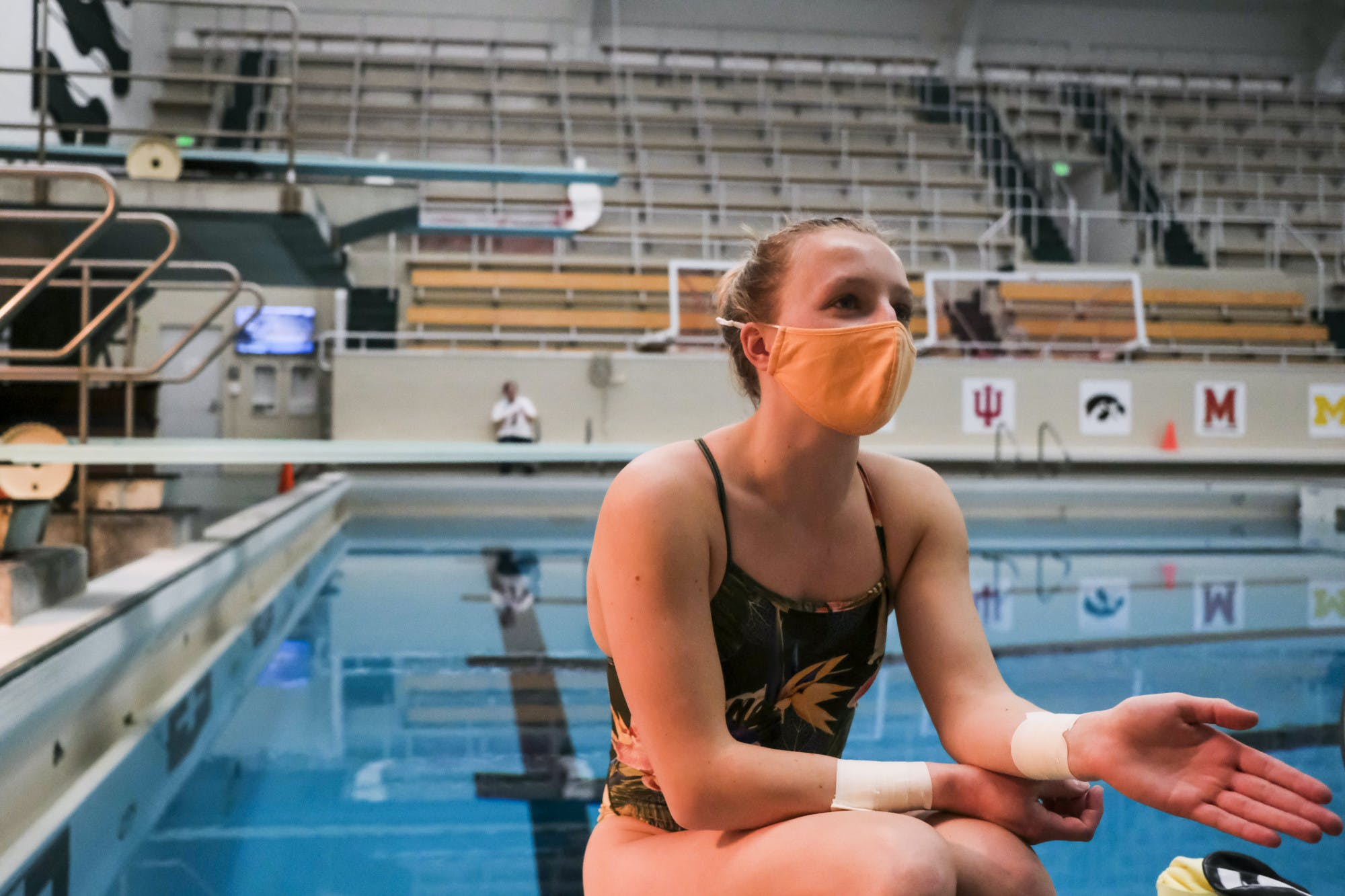 A person wearing a face mask and swimsuit sits in front of an empty pool with empty viewer stands.