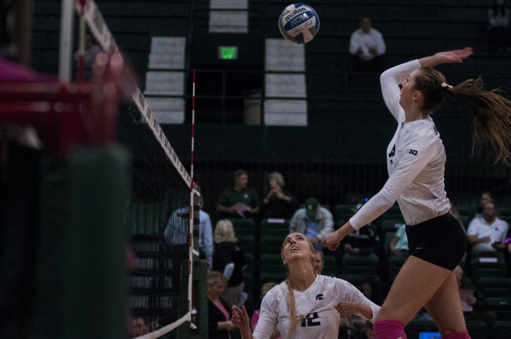 Junior setter Rachel Minarick (12) watches junior side hitter Rachel Minarick (12) hit the ball over the net during a warm-up before the game against Rutgers on Oct. 19, 2016 at Jenison Fieldhouse The Spartans defeated the Scarlet Knights, 2-1.