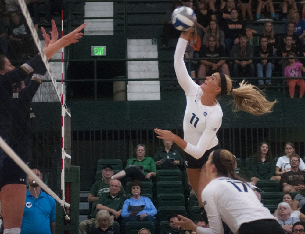 Senior outside hitter Chloe Reinig (11) spikes the volleyball during the volleyball game against Notre Dame on Sept. 16, 2016 at the Jenison Field House. The Spartans defeated the Fighting Irish, 3-0.