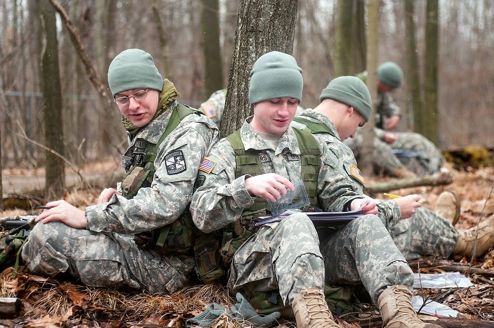 Engineering junior Andrew Cross, left, and political science junior Kyle Kueppers, right, talk during a plotting session at a wooded area owned by the Army ROTC on Dobie Road in Okemos on Tuesday, March 12, 2013. The cadets had ten minutes to plot coordinates on maps in order to find the points during a navigational skills test. Danyelle Morrow/The State News
