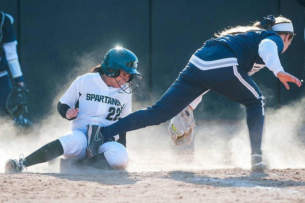 <p>Junior outfielder Dana Briggs scores a run by the home plate as she runs into a Penn State player  April 3, 2013, at Secchia Stadium at Old College Field. The Spartans defeated the Nittany Lions in the second game of the doubleheader, 7-1. Justin Wan/The State News</p>