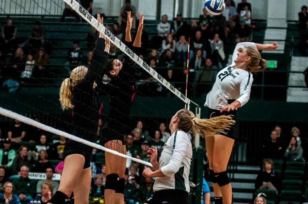 Freshman middle blocker Rebecka Poljan (21) hits the ball during the game against Rutgers on Sept. 29, 2018 at Jension Fieldhouse. The Spartans  the Scarlet Knights   .