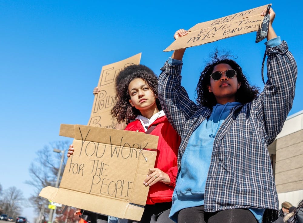 <p>Protesters Liyu Mesay, left, and Anaiss Rios-Kasoga, right, hold signs toward the road at the Lansing Police brutality protest in front of the East Lansing Police Station and 54B District Court on Feb. 23, 2020.</p>