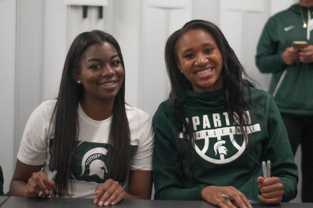 Red shirt senior guard Branndais Agee, left, and freshman forward Sidney Cooks sign autographs during Michigan State Madness on Oct. 20, 2017 at Breslin Center.