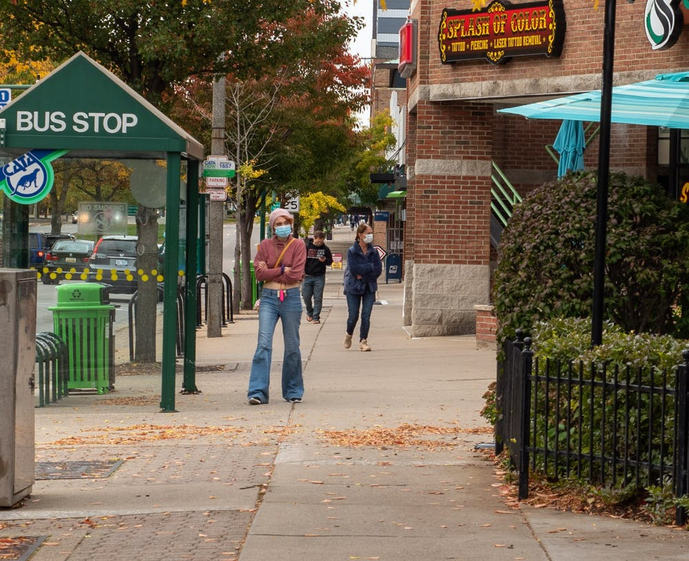 <p>Residents wearing masks in downtown East Lansing on Wednesday, Oct. 14, 2020.</p>