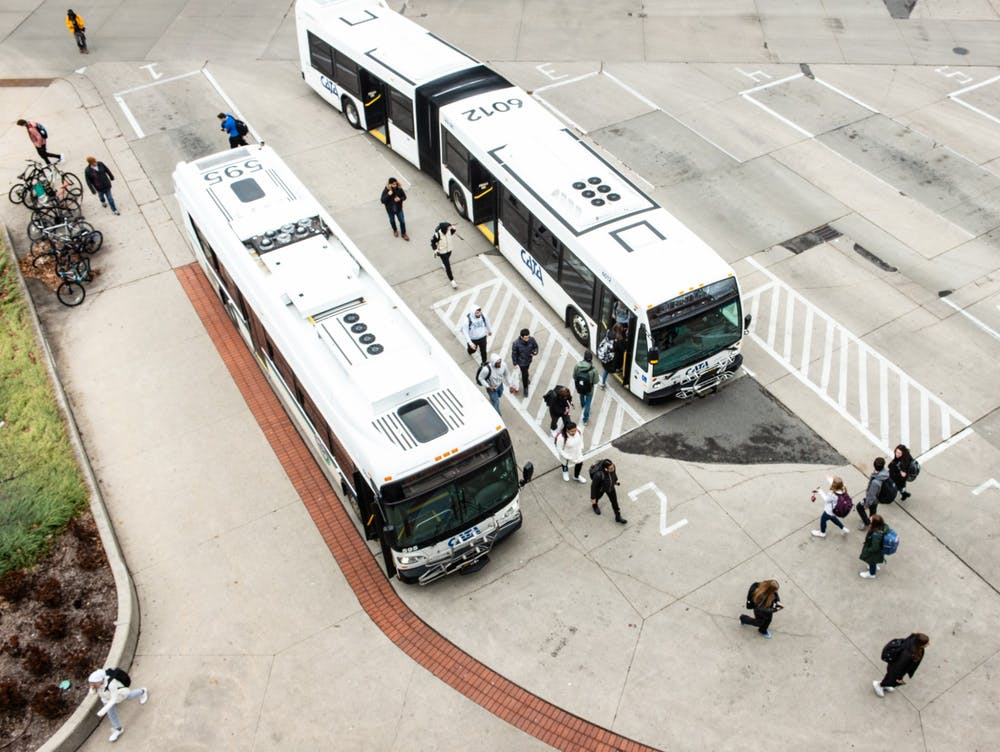 <p>Students get on and off CATA buses after an email was released notifying students that classes after noon have been cancelled on March 11, 2020.</p>