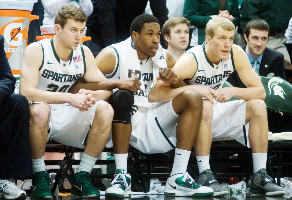 From left, senior guard Mike Kebler, junior forward Delvon Roe and junior guard Austin Thornton link arms with seconds left in the game as MSU trails Indiana, 79-78, Sunday at Breslin Center. A free throw kept the Spartans alive and took the game into overtime. MSU beat Indiana, 84-83. Kat Petersen/The State News