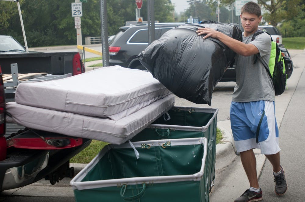 <p>Engineering freshman Cody Voelker begins to unpack his truck on Aug. 30, 2015, at Brody Complex. Courtney Kendler/The State News</p>