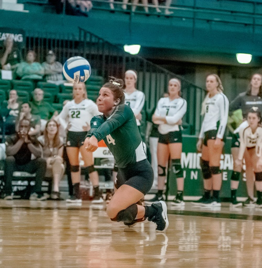 Sophomore defensive specialist and libero Jamye Cox (4) bumps the ball to her teammate during the game against Albany on Sept. 14, 2018 at Jenison Fieldhouse. The Spartans defeated the Great Danes, 3-0.