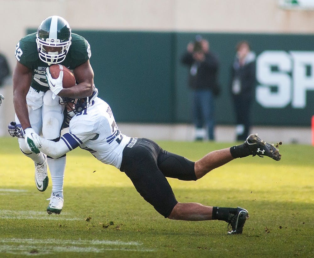 <p>Senior running back Larry Caper gets tackled by cornerback Quinn Evans on Saturday, Nov. 17, 2012, at Spartan Stadium. The Spartans&#8217; fell to Northwestern 23-20. James Ristau/The State News</p>