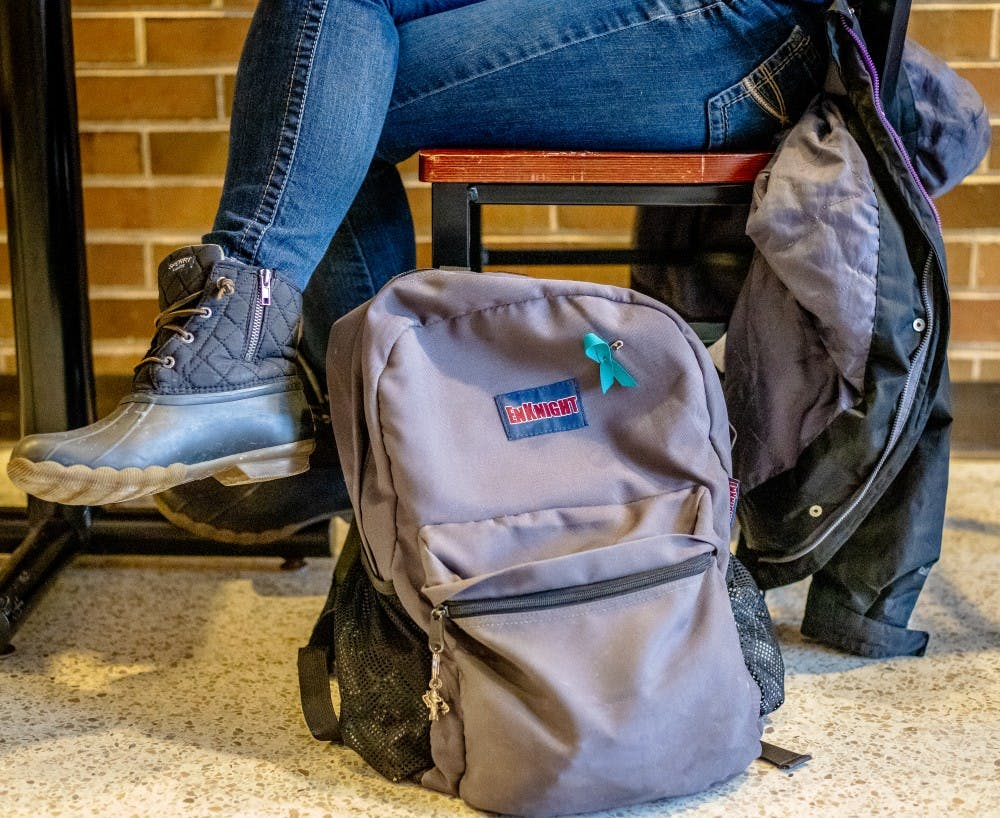 <p>Communications junior Maddie Jones rests her backpack, pinned with her teal ribbon, next to her while she studies on Jan. 22, 2019 at the Communication Arts and Sciences Building.</p>