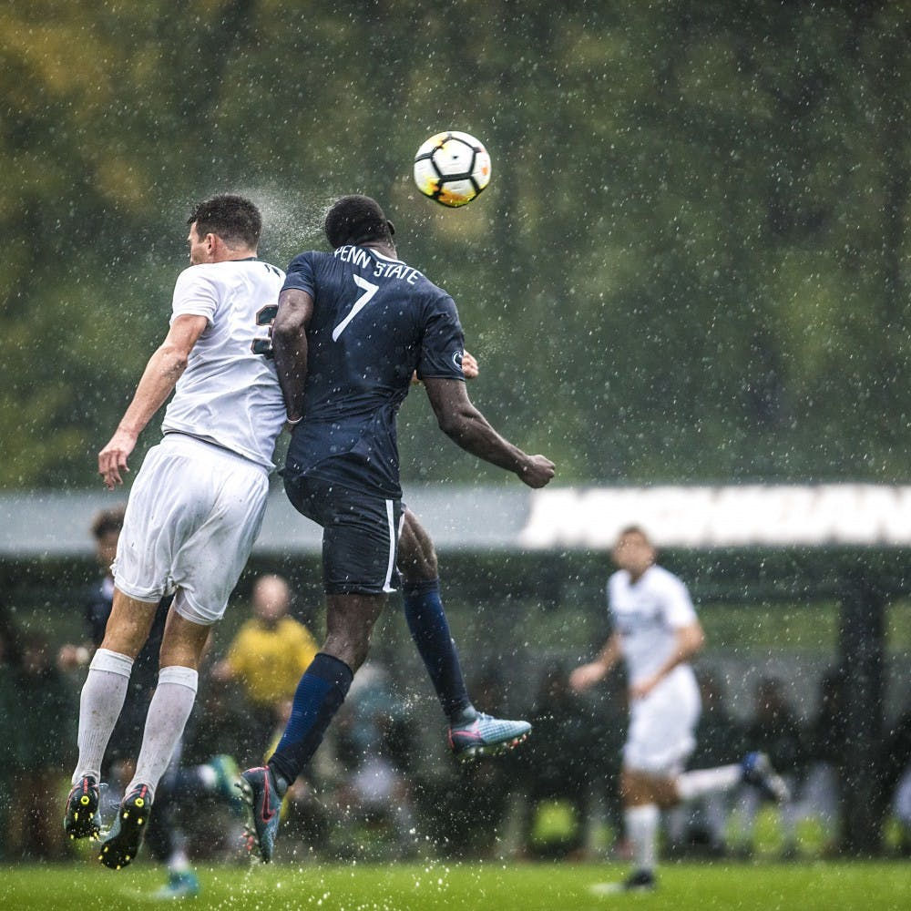 Penn State forward Aymar Sique (7) heads the ball during the game on Oct. 14, 2017 at DeMartin Stadium. The Spartans defeated the Nittany Lions in the pouring rain, 1-0.