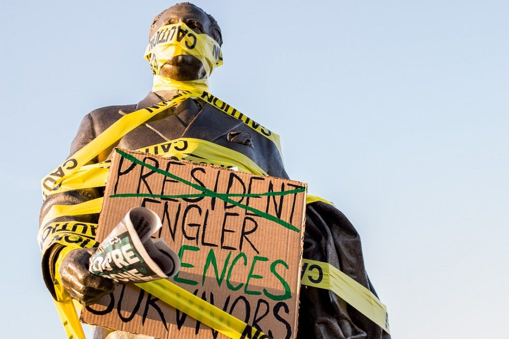 <p>The statue of John A. Hannah stands wrapped with caution tape on April 20, 2018 at the Hannah Administration Building. The rally was organized by students and Nassar survivors to call for the resignation of the Board of Trustees.</p>