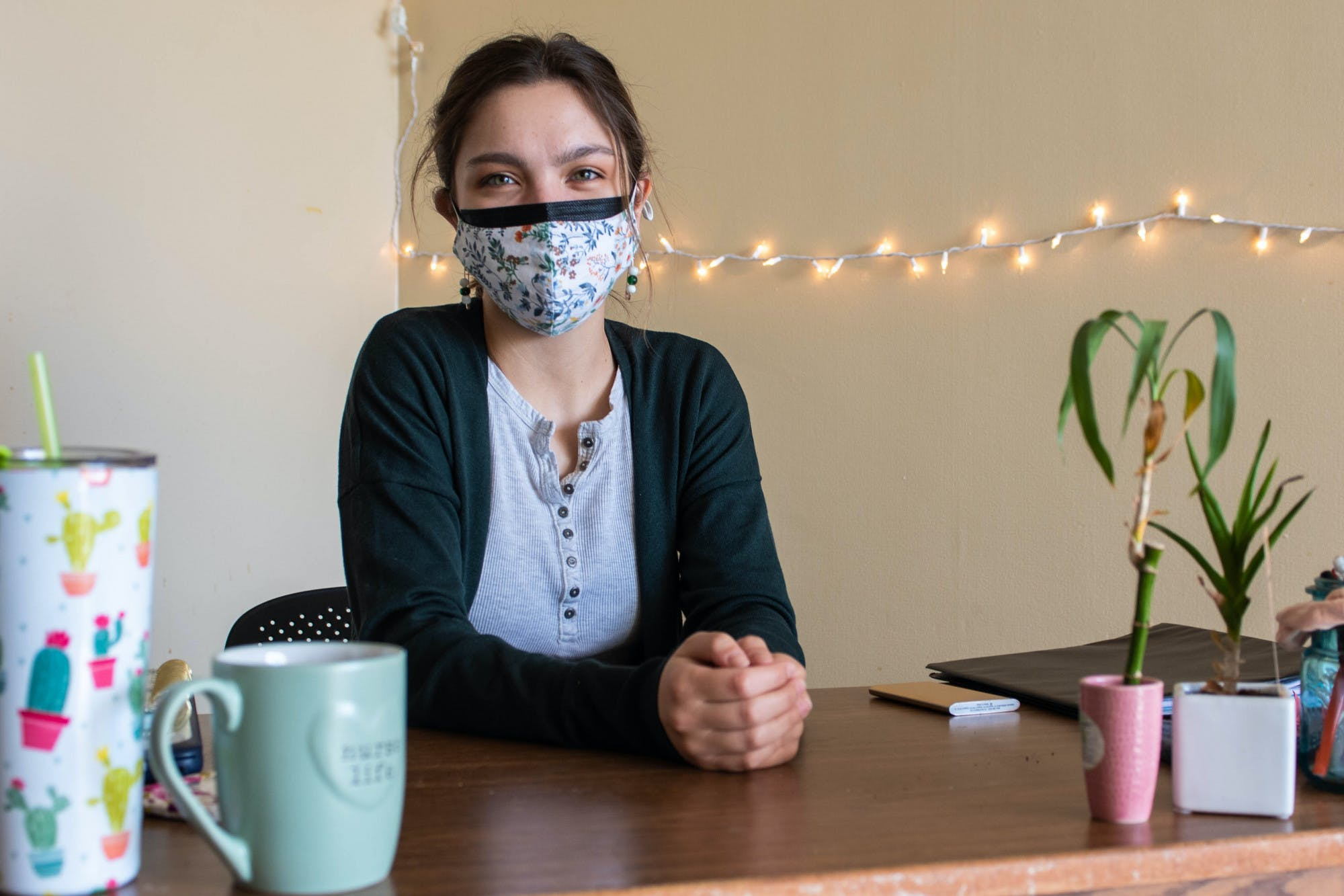 A person wearing two face masks, one with a floral pattern, poses for a photo while sitting at a desk. On the desk are plants, notebooks and mugs. Behind the person is a wall where a strand of white string lights hang.