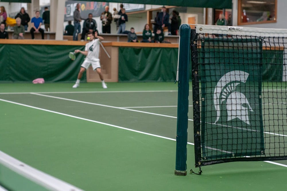 Sophomore Ivan Rakic hits the ball during a singles match at the MSU Tennis Center on Jan. 12, 2019.