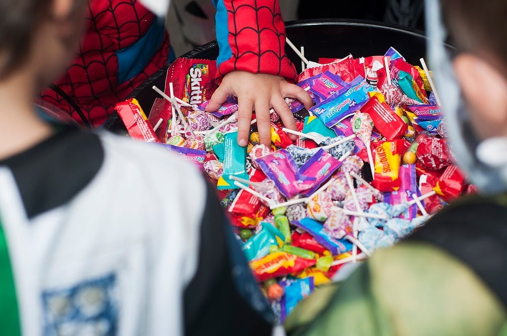 <p>Trick-or-treaters grab candy during Trick-or-Treat on the Square, Oct. 28, 2013, on South Washington Square in downtown Lansing. Kids of all ages came out to participate in various activities while going from station to station for candy. Danyelle Morrow/The State News</p>