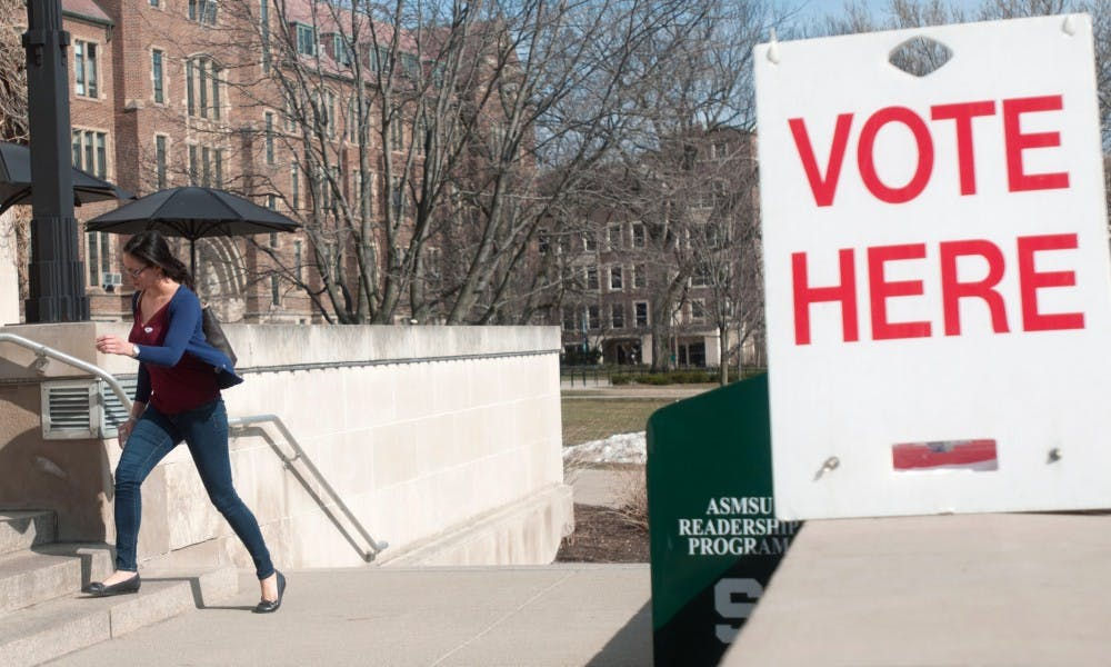 Communication senior Kim Nguyen walks by a voting sign on March 8, 2016 on the steps of the MSU Union. Nguyen voted earlier today in the Michigan presidential primary election.