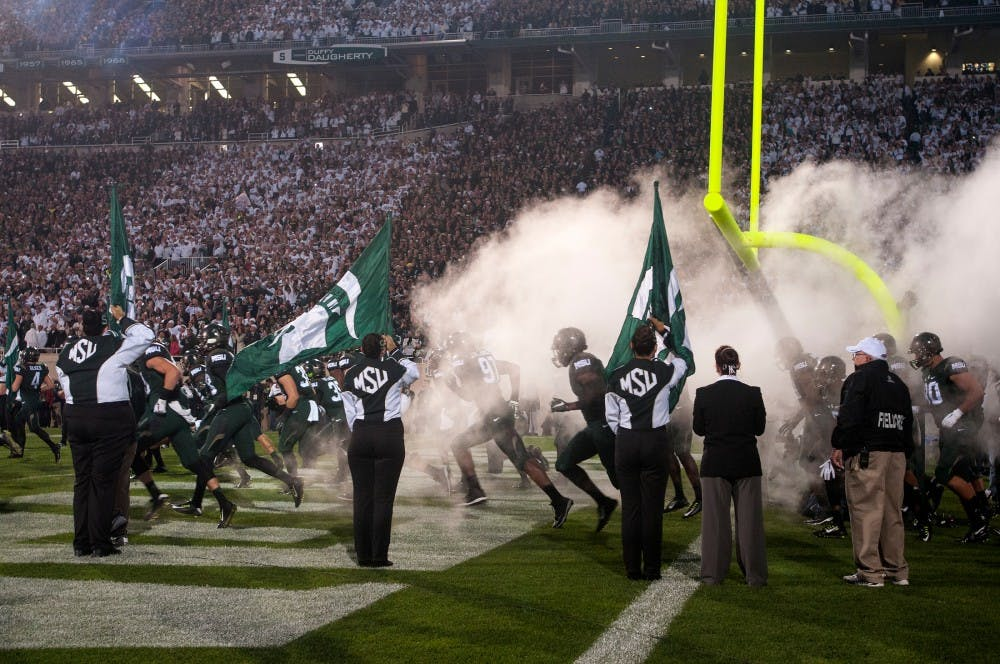 <p>The Spartans enter the stadium in a cloud of smoke at the start of the game against Oregon on Sept. 12, 2015 at Spartan Stadium. The Spartans defeated the Ducks 31-28. Catherine Ferland/ The State News</p>