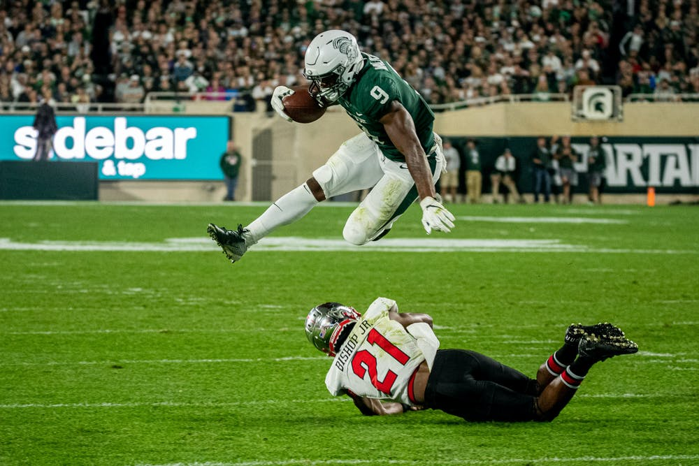 <p>Junior running back Kenneth Walker III hurdles a Western Kentucky defender on his way to the end zone during the Spartans&#x27; homecoming game on Oct. 2, 2021.</p>