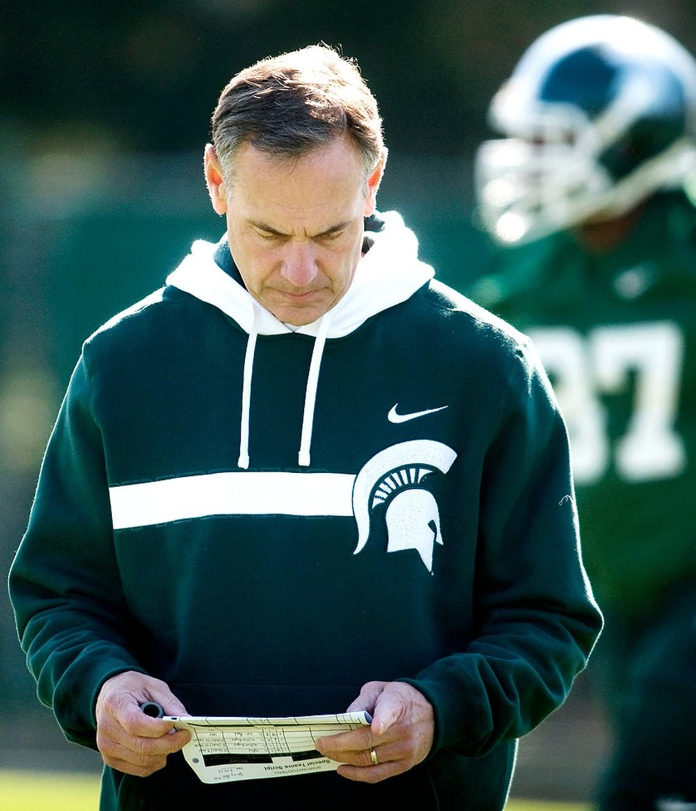<p>Head coach Mark Dantonio looks over paper work during practice April 17, 2012, at the practice fields outside of the Duffy Daughtery Building. Samantha Radecki/The State News</p>