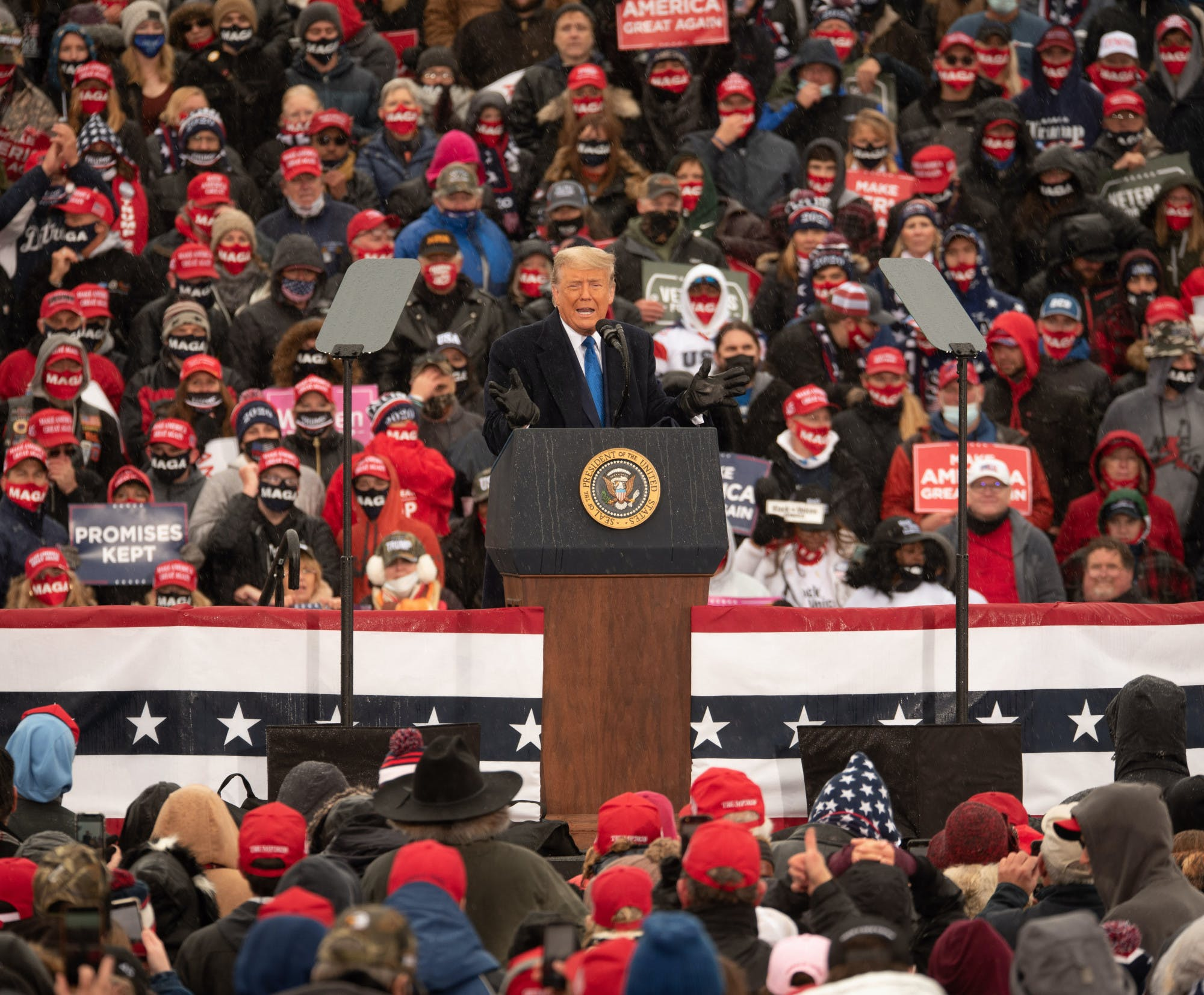 Then-President Donald Trump stands and speaks at a podium among a crowd of people wearing red hats and Trump clothing.