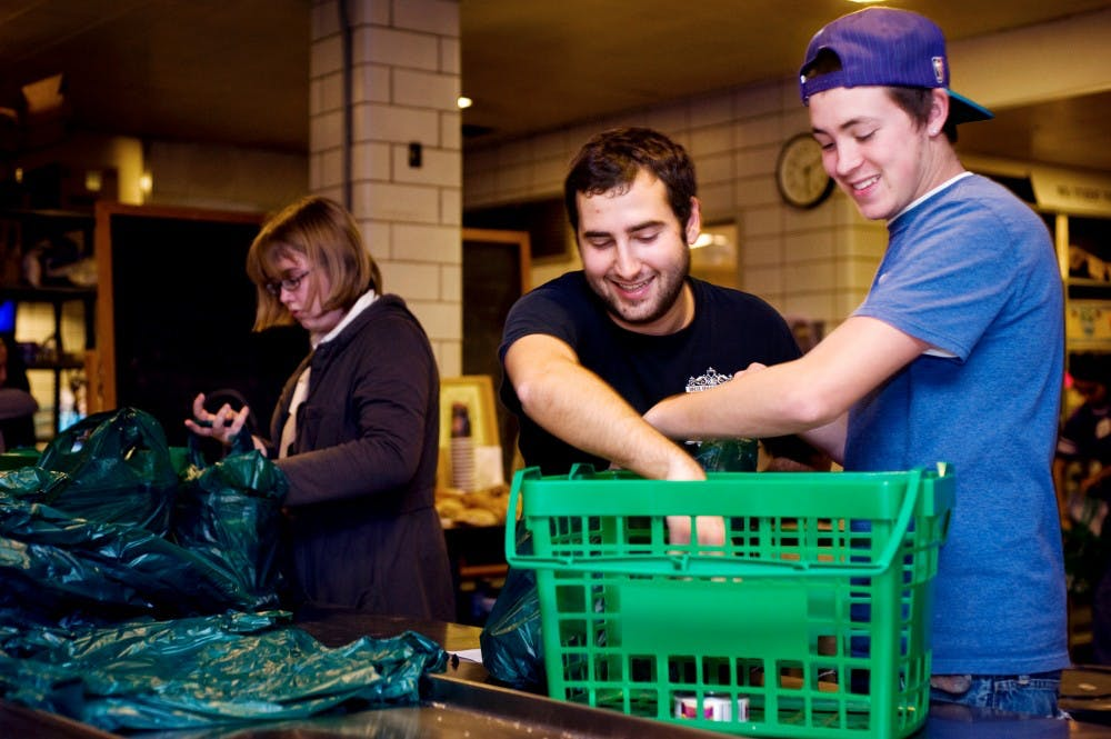 Physiology senior Alex Hoelzel, left, and kinesiology junior Justin Collins, right, volunteer and bag up food at the MSU Student Food Bank on Wednesday evening. Lauren Wood/The State News