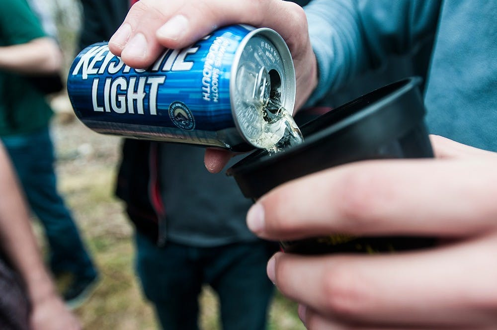 <p>Ferris State University student Alex Kallenbach pours beer into a cup April 12, 2014, at Nachofest at a house on Stoddard Ave. Nachofest is an annual party where tortilla chips and nacho cheese are provided. Erin Hampton/The State News</p>