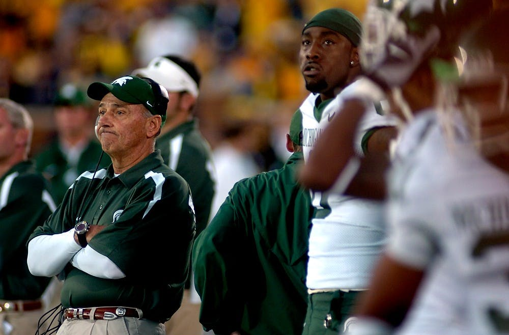 <p>An injured Matt Trannon stands behind Head Coach John L. Smith as the clock winds down on MSU hopes of beating of Michigan on Oct. 7, 2006. The Spartans lost, 31-13. Katie Rausch/The State News</p>