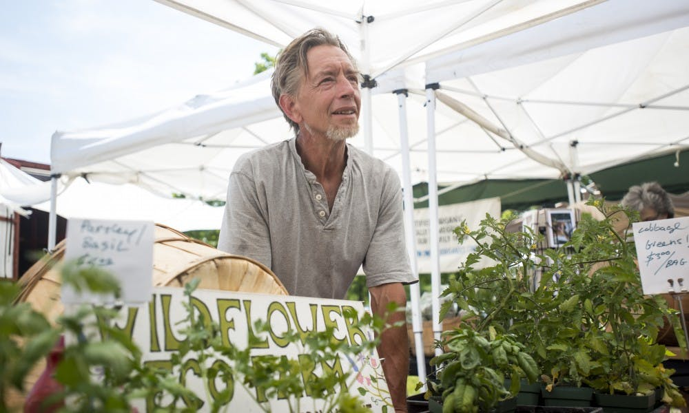 <p>Phil Throop from Wildflower Eco Farm introduces a product to a customer during the East Lansing Farmer's Market on June 4, 2017 at Valley Court Park. The East Lansing Farmer's Market is a growers-only market and every item sold by vendors is homegrown.&nbsp;</p>