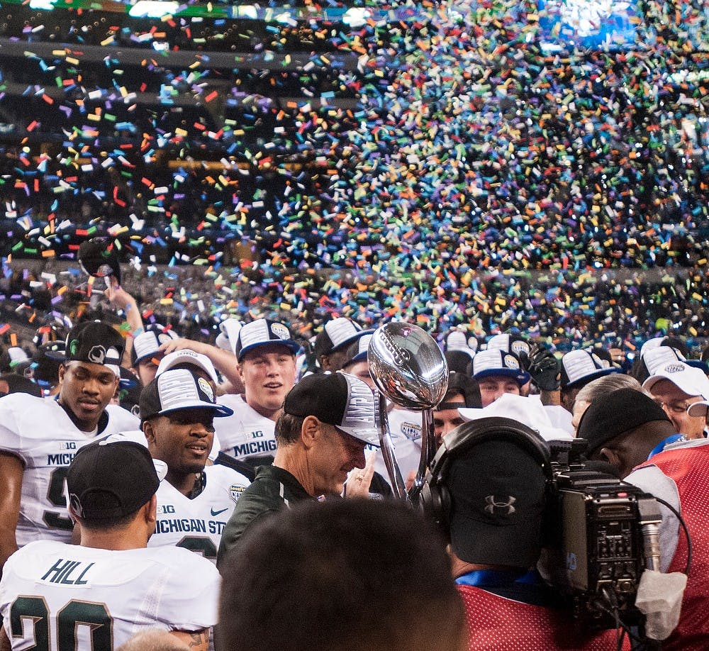 <p>Head coach Mark Dantonio holds the trophy and celebrates the win with his team Jan. 1, 2015, during The Cotton Bowl Classic football game against Baylor at AT&T Stadium in Arlington, Texas. The Spartans defeated the Bears and claimed the Cotton Bowl Victory, 42-41. Erin Hampton/The State News</p>