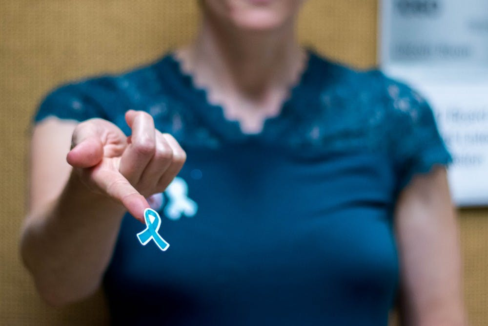 Betsy Riley of Reclaim MSU passes out teal ribbons at the Kellogg Conference Center on Oct. 11, 2018. Teal ribbons are the symbol of support for sexual assault survivors.