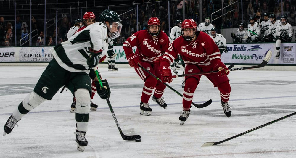 <p>Freshman forward Kyle Haskins (17) navigates through the Wisconsin defense in the first period. The Badgers shutout the Spartans 4-0 at Munn Ice Arena on Mar. 5, 2021. </p>