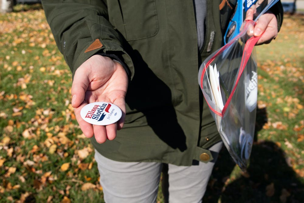 <p>Taylor Sullivan, a visibility volunteer for Elissa Slotkin, hands out pins outside of the South Washington Elections Unit in Lansing, Michigan, on Nov. 3, 2020.</p>