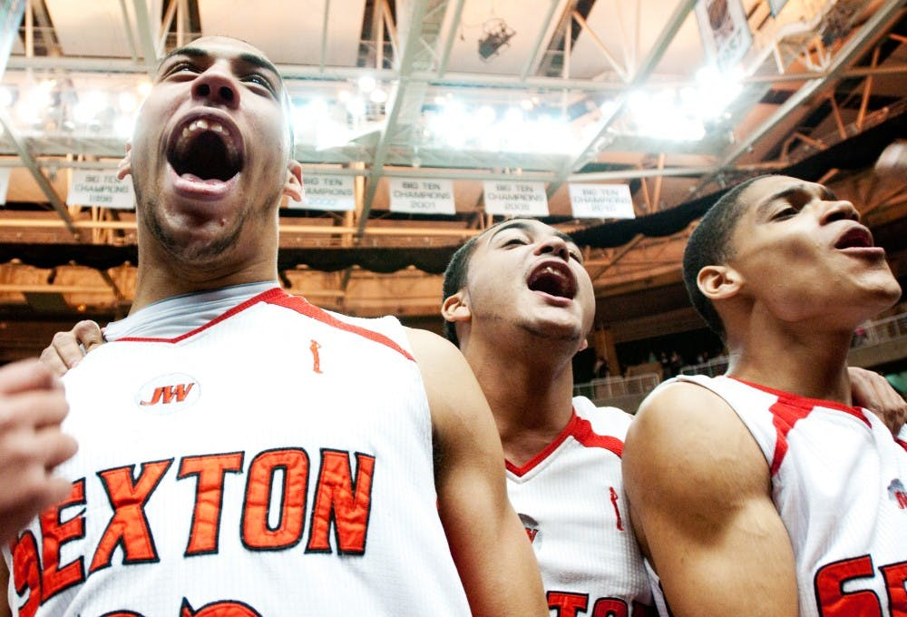 MSU recruit Denzel Valentine of Lansing Sexton, left, celebrates with his teammates after winning the MHSAA Class B Final game against Muskegon Heights on Saturday afternoon at Breslin Center. Josh Radtke/The State News
